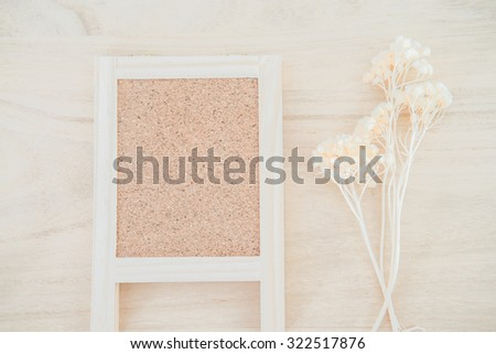 Wood cork board on wood texture background with dried flower - stock photo