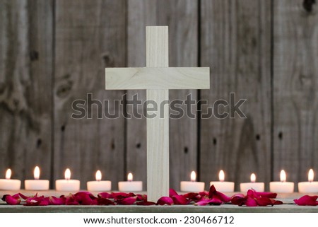 Wood cross by candlelight and rose petals with rugged wooden background - stock photo