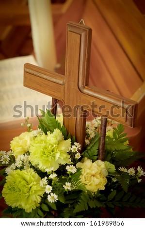 wood cross with beautiful green flowers - stock photo