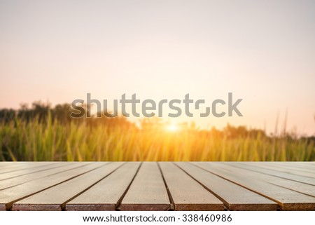 wood desk space and rice field background. for product presentation.