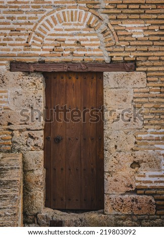 Wood door in brick wall of ancient Spanish building