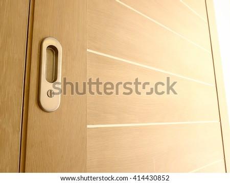 Wood door slide with soft sunlight, modern style, Metal door handles - stock photo