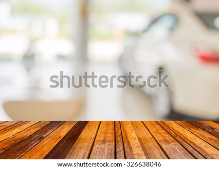 wood floor and blur image of Commercially cars stand in show room of car shop for background usage. - stock photo