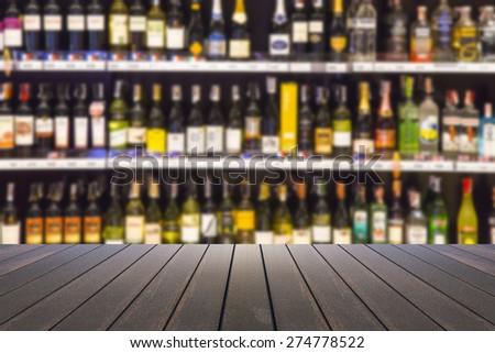 wood floor and wine Liquor bottle on shelf - Blurred background - stock photo