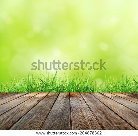 Wood floor with green bokeh  and  Fresh spring green grass and sunlight  . Beauty natural background