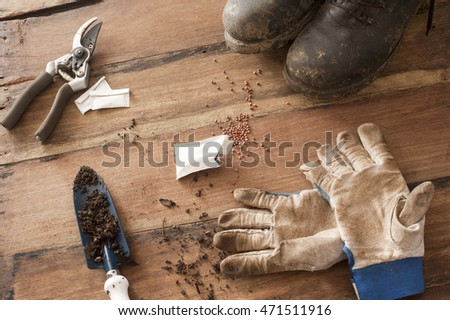 Wood floor with muddy black boots and garden sheers next to open seed packet and gloves by trowel with dirt