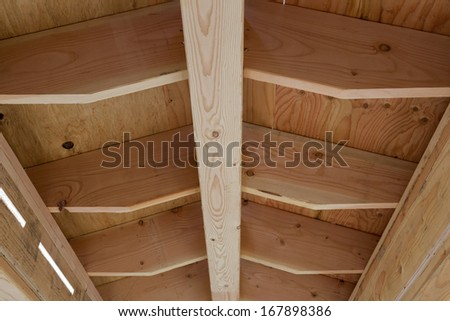 Wood frame of a house roof under construction - stock photo