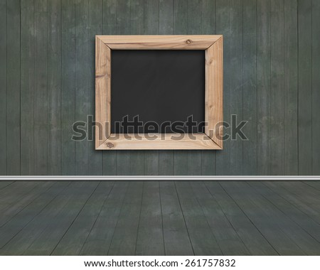 Wood frame of blank blackboard with dark green wooden wall and floor background - stock photo