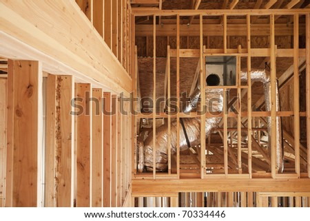 Wood framing and ventilation in a home under construction. - stock photo