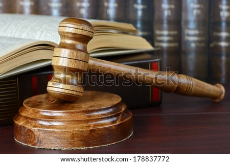 Wood gavel, soundblock and open book on the background of shelves of old books - stock photo
