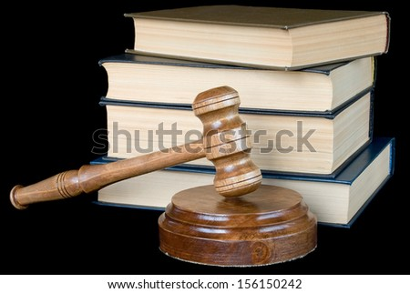 Wood gavel, soundblock and stack of thick old books on a black background