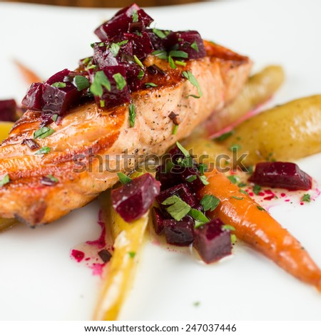 Wood Grilled Organic Salmon with fingerling potatoes, baby carrots and roasted baby beet vinaigrette - stock photo