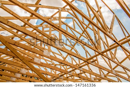 Wood house truss against blue sky with puffy clouds - stock photo