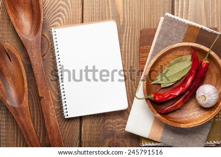 Wood kitchen utensils over wooden table background with notepad for copy space - stock photo