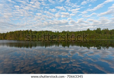 Wood lake with reflections of clouds in water - stock photo
