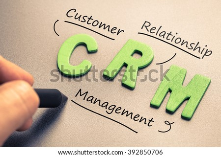 Wood letter of CRM abbreviation (Customer Relationship Management) with hand writing definition