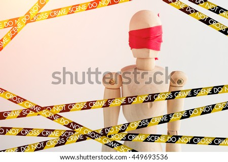 wood man figure blind with red ribbon with police line crime scene tape  and copy space for your idea - stock photo