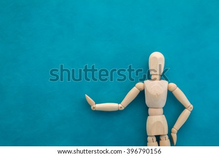 wood man figure presenting and showing something on color background - stock photo