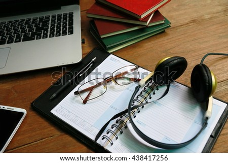 Wood office desk table with a lot of things on it. Top view. Blank laptop and phone,Layout of comfortable working space on wooden, internet laptop headphone phone notepad pen eyeglasses  laying on it