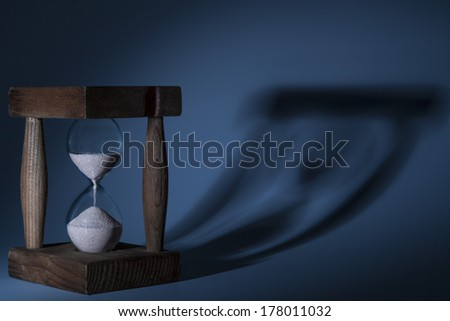 Wood old brown Hourglass with blue lightning with shadow - stock photo
