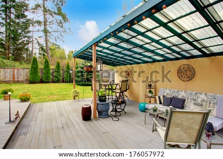 Wood patio pergola with iron table set, sofa and chairs overlooking beautiful green lawn and fir trees. Patio area decorated with iron arts and flower pots. - stock photo