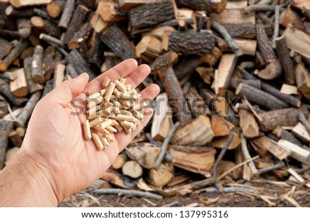 Wood pellets in hand on firewood background - stock photo