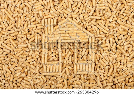 wood pellets in the shape of a house on wood pellets surface - stock photo