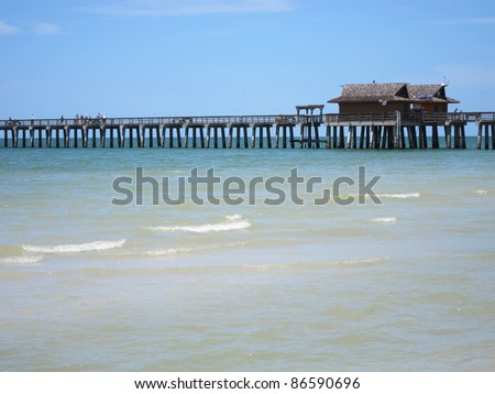 wood pier by beach in Naples Florida - stock photo