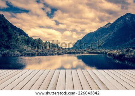wood plank platform with lake and mountains reflections vintage style - stock photo