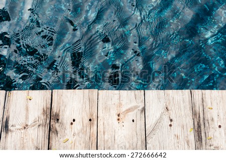 Wood planks against blue water background - stock photo