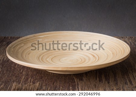Wood plate on wooden table over grunge background, rustic style - stock photo