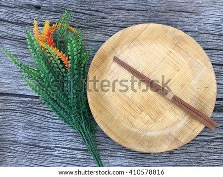 Wood plated and chopstick and flowers on wood background - stock photo