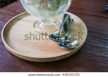 wood saucer ice cream with silverware on wood table