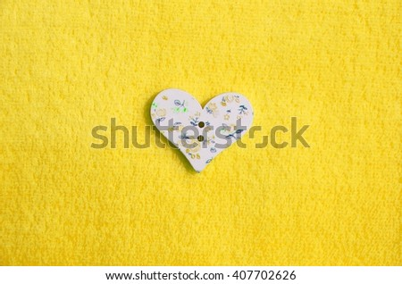 Wood sewing buttons scrapbooking pattern of small flowers in the shape of a heart love is a juicy, bright, beautiful yellow background. Background for cards, place for text - stock photo
