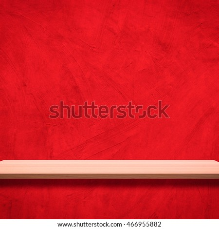 Wood shelves empty on a background of red cement wall.
