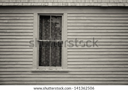 Wood siding New england coastal home with a wooden window and sheen see through daisy flowered curtains - stock photo