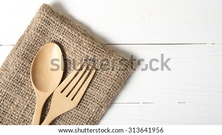 wood spoon and fork on kitchen towel over white background