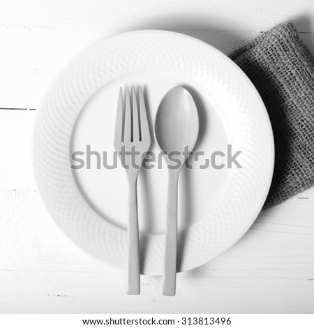 wood spoon and fork with dish over table background black and white tone color style
