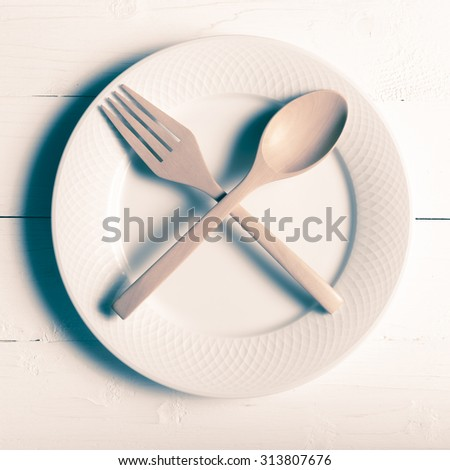 wood spoon and fork with dish over table background vintage style