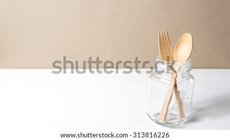 wood spoon and fork with glass over white table