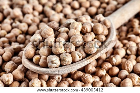 Wood spoon full of chick peas beans. Chick-pea background. Nut is a main ingredient of hummus and many other vegan dishes. - stock photo