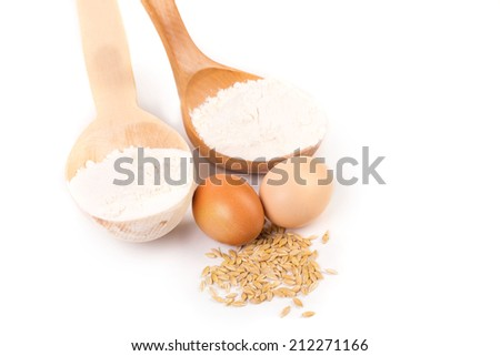 Wood spoon with eggs and grains. Isolated on a white background.