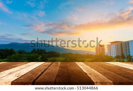 wood table and blur mountain with sunset sky.