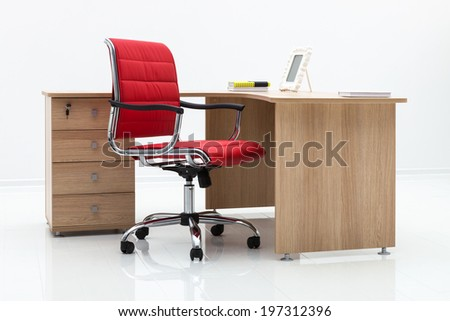 wood table and red chair on a white wall