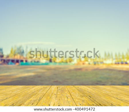 wood table and vintage tone blur image of property construction site and clear blue sky for background usage .