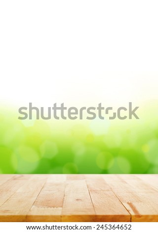 Wood table top on abstract white & green bokeh background - stock photo