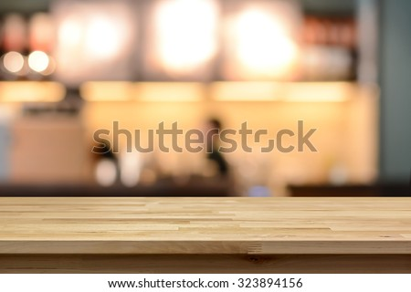 Wood table top on blur cafe ( coffee shop) interior background - can be used for display or montage your products - stock photo
