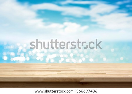 Wood table top on blur shiny sea water and summer sky background - can be used for display or montage your products - stock photo