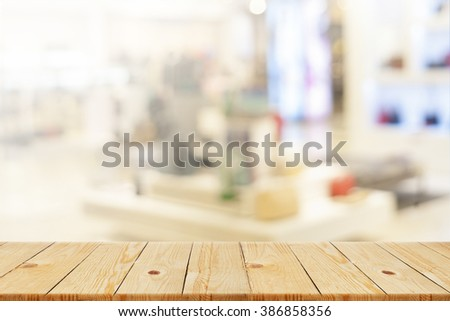 Wood table top on blur shopping mall background - can be used for display or montage your products - stock photo