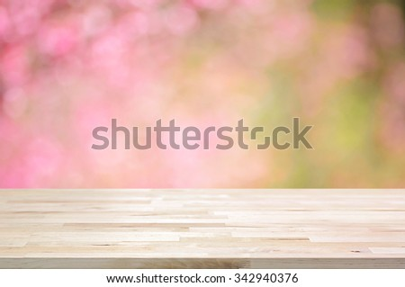 Wood table top on blurred background of pink cherry blossom flowers - can used for display or montage your products - stock photo